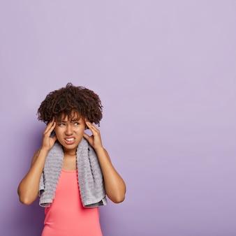 스포티 한 불쾌한 아프리카 계 미국인 여성이 너무 많은 운동으로 편두통에 걸렸습니다.