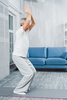 Sporty elderly man practicing yoga indoors