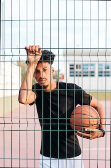 Sporty ethnic man holding basketball behind fence