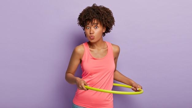 La donna etnica sportiva con l'acconciatura riccia mantiene le labbra arrotondate, ruota l'hula hoop, è in buona forma, indossa un gilet rosa casual, ha un corpo atletico