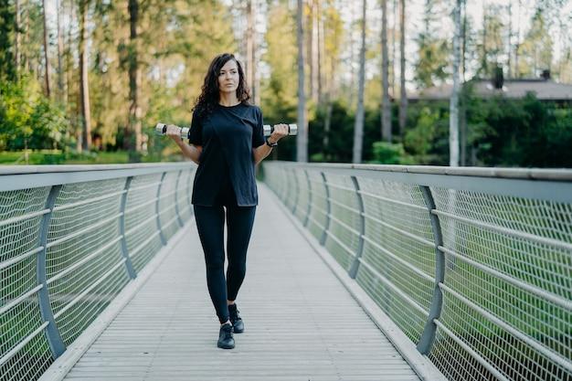黒のtシャツとレギンスでスポーティなヨーロッパの女性が橋を渡って歩く2つのダンベルを保持します