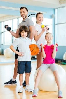 スポーティな家族。ヘルスクラブで互いに近くに立っている間、さまざまなスポーツ用品を持っている幸せな家族