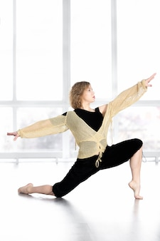 Dancing femminile sportiva, equilibrando in posa lunga in classe
