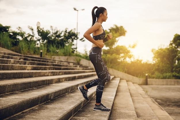 Sporty female runner running downstairs sun set