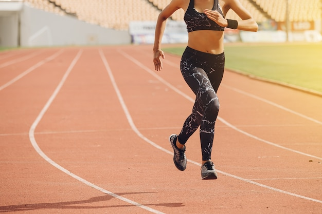 Sporty female runner running on stadium track