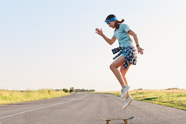 Sporty female wearing t shirt and short doing tricks on a skateboard on street on asphalt road, jumping in the air, enjoying skateboarding alone in sunset in summertime.