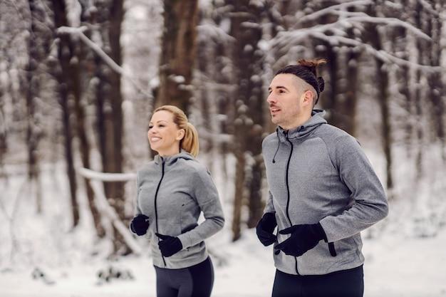 스포티 한 커플 눈 덮인 겨울 날 숲에서 함께 조깅. 관계, 야외 피트니스, 건강한 삶