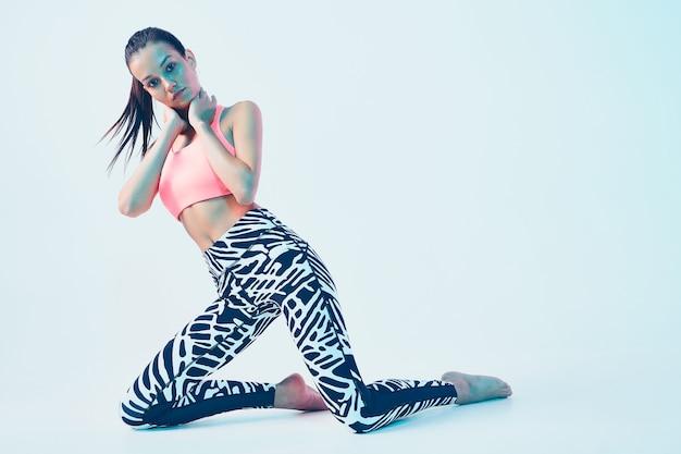 ネオンライトでスタイリッシュなスポーツウェアのスポーティなフィットの女の子。効果的なトレーニング、健康的なスポーツのためのレギンス