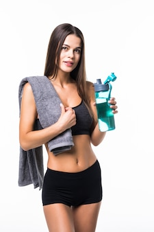 Sporty fit muscular woman drinking water, isolated against white