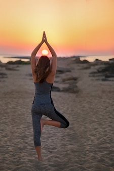 Sporty fit woman doing hatha yoga asana vrikshasana tree pose on tropical beach on sunset