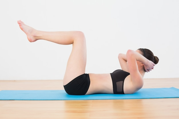 Sporty fit woman doing sit ups on in fitness studio