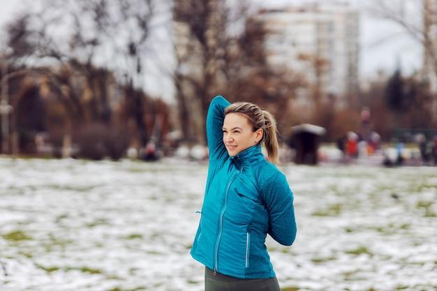 눈 덮인 겨울 날 공공 공원에 서 있는 동안 팔을 위한 스트레칭 운동을 하는 스포티한 여성. 겨울 피트니스, 눈, 쌀쌀한 날씨