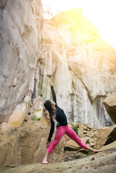 Sporty fit woman is practicing yoga on the boulder in the nature