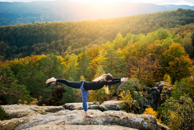 Sporty fit woman is practicing yoga on the top of the mountain