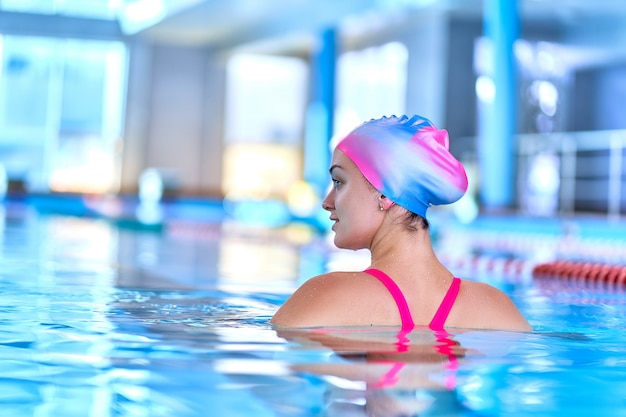 Sporty fit woman in swimming hat and swimsuit learns to swim in sports pool in leisure center