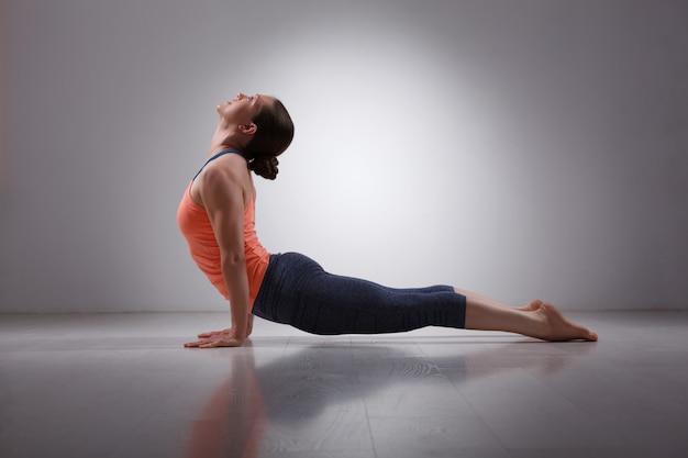 Sporty fit yogini woman practices yoga asana urdhva mukha svanas