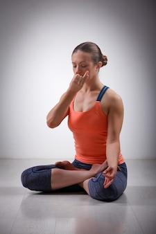 Sporty fit yogini woman practices yoga pranayama breath control