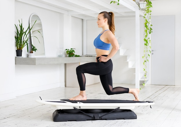 Sporty fit young woman doing a static lunge pose on a surfset in a high key gym with plants