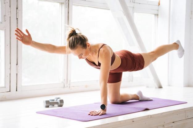 Спортивная подтянутая молодая женщина с совершенным спортивным телом в спортивной одежде делает упражнения на растяжку на подоконнике во время тренировки. концепция здорового образа жизни и физической активности дома.
