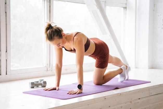 窓枠でスポーツウェアのトレーニングトレーニングを身に着けている完璧なアスリートボディを持つスポーティフィットの若い女性。健康的なライフスタイルと家庭での身体活動の概念。