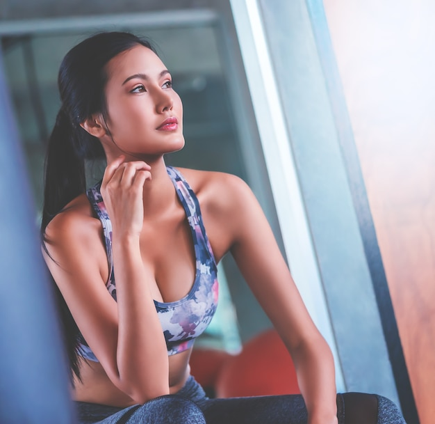 Sporty fitness asian woman is sitting and relaxing in boxing fitness gym.