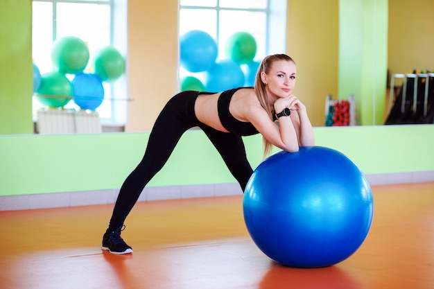 Sporty fitness woman in the gym with big gumnastic ball.