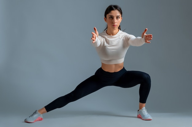 Sporty girl doing bodyweight lateral split squats on grey wall
