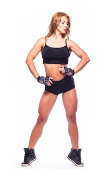 Sporty girl doing boxing exercises, making direct hit. young girl isolated on white wall. strength and motivation.