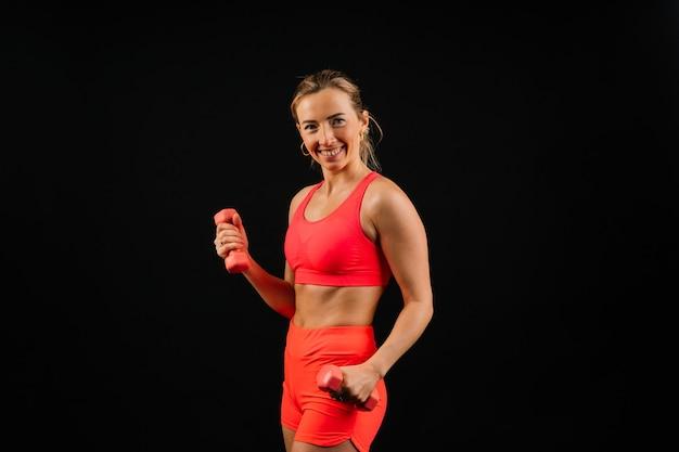 ダンベルで運動をしているスポーティな女の子、暗くて白い背景の上に撮影されたシルエットスタジオ