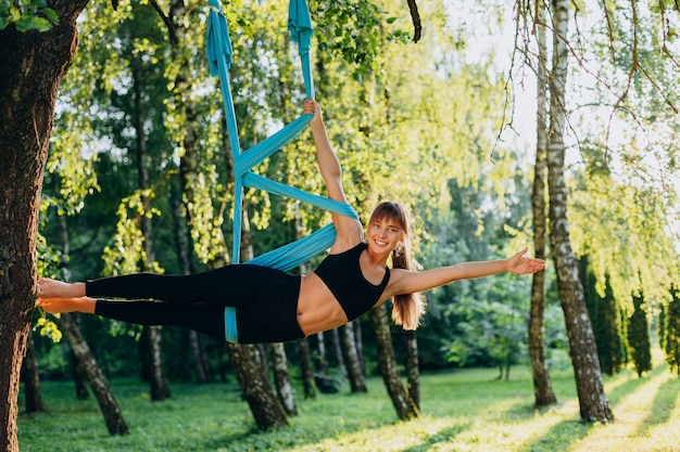 Sporty girl doing fly yoga  in side pose outdoors looking at the camera