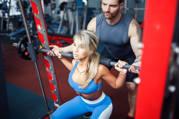Sporty girl doing squat exercises with assistance of her personal trainer at gym.