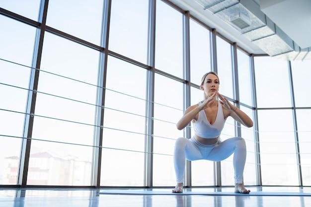 Sporty girl doing squat exercises