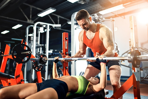 Sporty girl doing weight exercises with assistance of her personal trainer at gym.