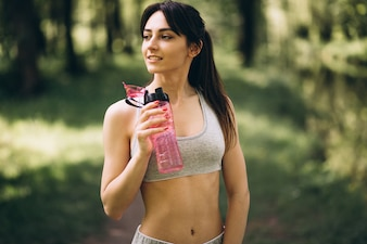 Sporty girl drinking water in park