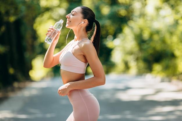 Sporty girl in earphones  drinks water standing in the park outdoor .