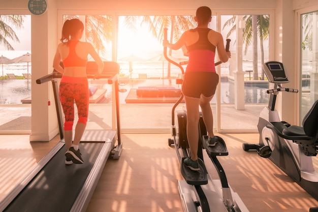 Sporty girl exercise on elliptical cross trainer and treadmill at gym