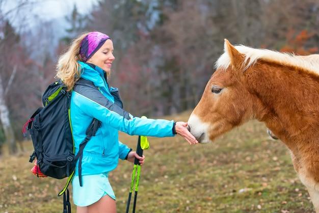 Спортивная девушка дает траву съесть лошадь