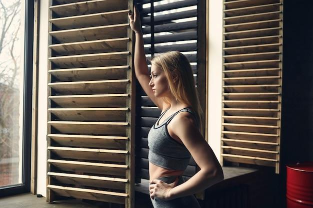 開いた窓に立って新鮮な空気を呼吸する運動の後に休憩を持っているスポーティな女の子。