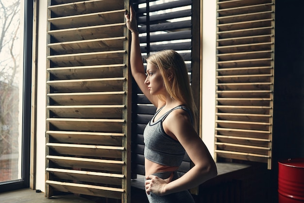 Ragazza sportiva che ha pausa dopo esercizi fisici respirando aria fresca in piedi alla finestra aperta.