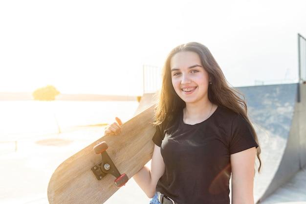Спортивная девушка держит ее скейтборд на открытом воздухе