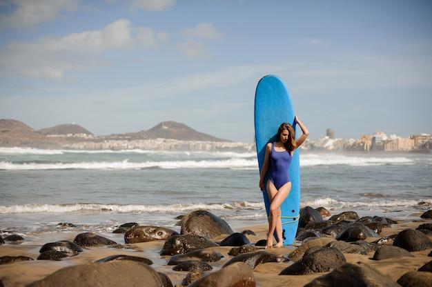 Спортивная девушка в синем купальнике стоит на доске для серфинга над атлантическим океаном