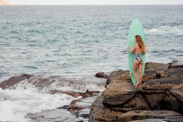 녹색 서핑을 들고 대서양 해변에 바위에 서있는 멀티 컬러 수영복에 스포티 한 소녀