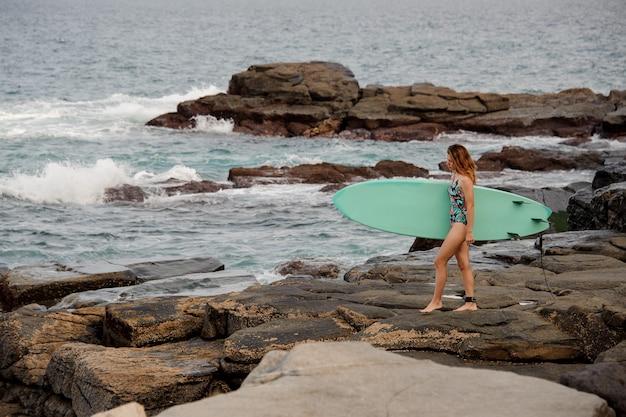 대서양 해변에서 바위에 서핑 보드와 함께 산책하는 멀티 컬러 수영복에 스포티 한 소녀