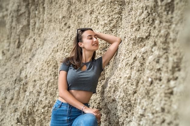 상단 및 모래 산 채석장에서 여름에 포즈를 취하는 청바지에 스포티 한 소녀. 건강한 생활