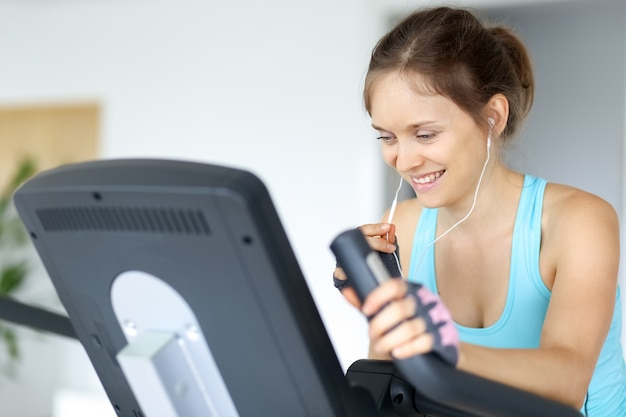 Sporty girl listening to music and training in gym