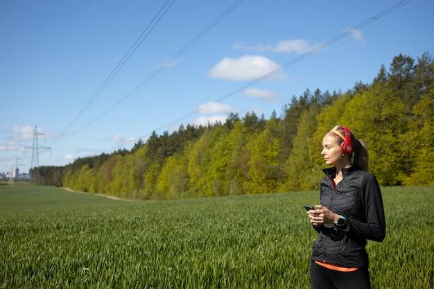Спортивная девушка слушает музыку на открытом воздухе