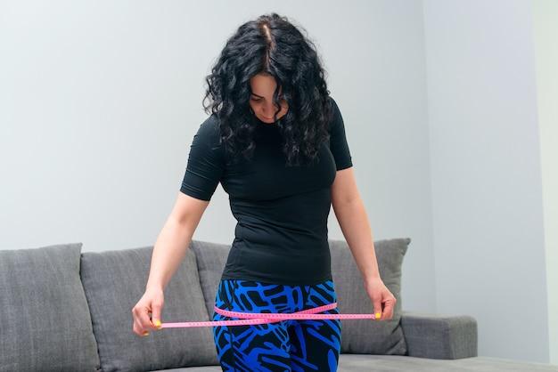 メートル法の巻尺で彼女の足を測定するスポーティな女の子