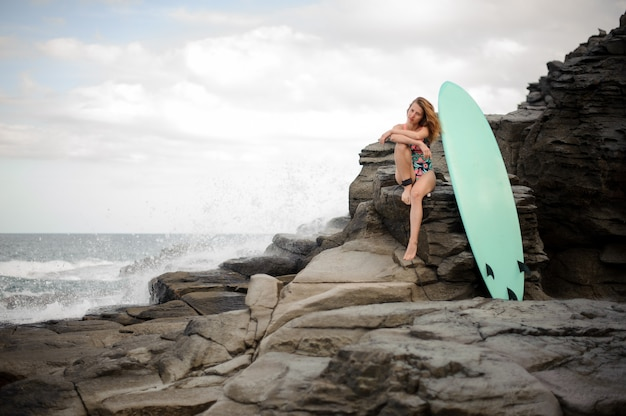 Sporty girl in the multi colored swimsuit sitting near the surfboard on the rock over the atlantic ocean and clear sky