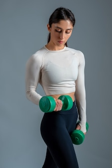 Sporty girl performing arm exercises with dumbbells on grey wall