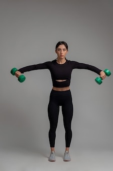 Sporty girl performing dumbbell lateral raise on grey surface